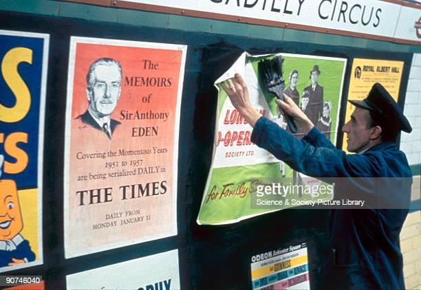 A billposter is shown pasting posters on the walls of a platform in Piccadilly Circus station including one advertising the serialisation of the...