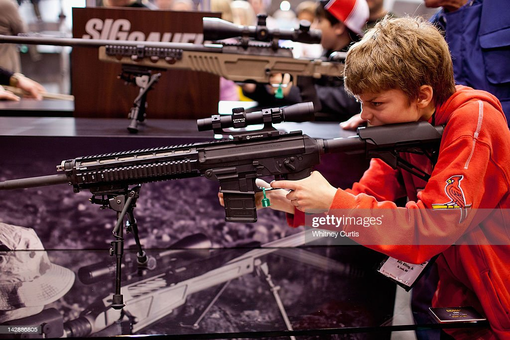 Billy Bitting Jr handles a SIG Sauer SIG556 semiautomatic rifle during the NRA Annual Meetings and Exhibits April 14 2012 at America's Center in St...