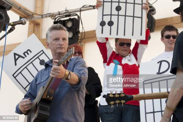 Billy Bragg and members of the audience holding up guitar chord diagrams perform on stage at the Village Green Festival on September 29th 2009 in...