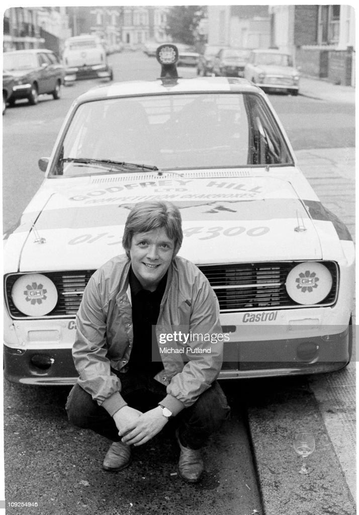 Billy Bremner of Rockpile, portrait with Ford Escort car, London, 1982.