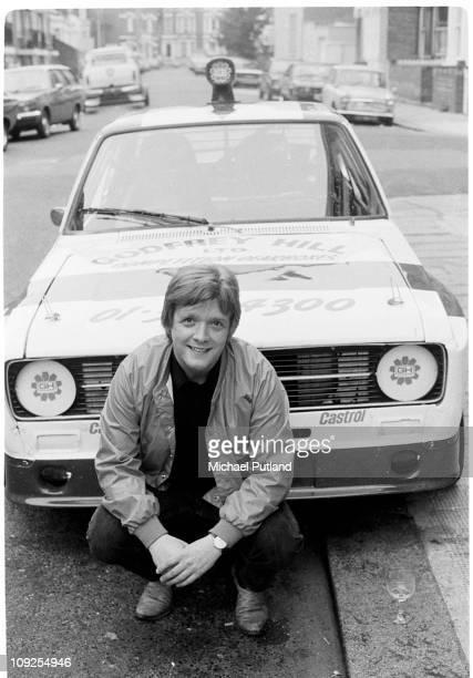 Billy Bremner of Rockpile portrait with Ford Escort car London 1982