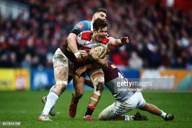Billy Burns of Gloucester is tackled by James Lang and Alofa Alofa of Halequins during the Aviva Premiership match between Gloucester Rugby and...