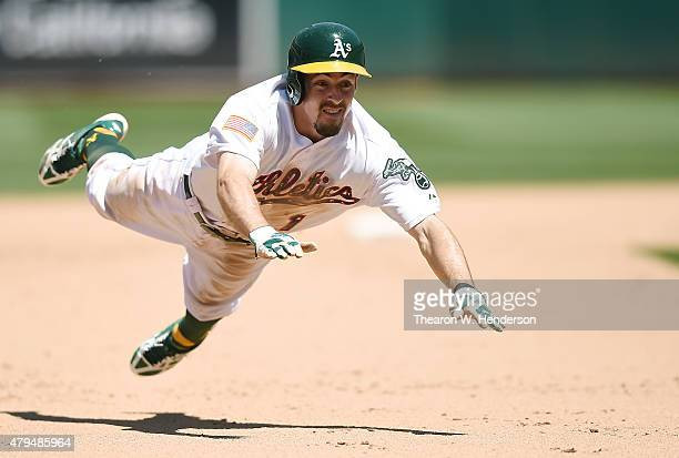 Billy Burns of the Oakland Athletics dives into third base safe against the Seattle Mariners in the bottom of the seventh inning at Oco Coliseum on...