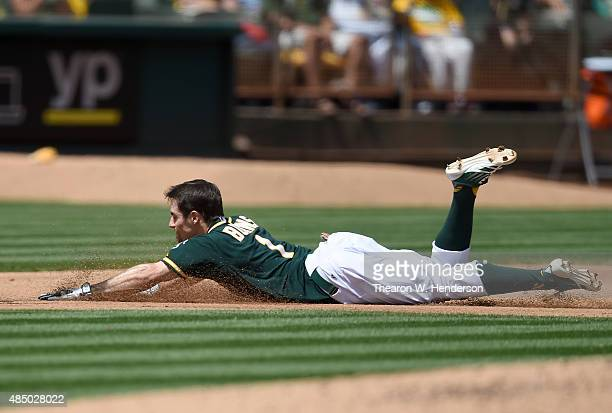 Billy Burns of the Oakland Athletics dives into third base with a triple against the Tampa Bay Rays in the bottom of the fourth inning at Oco...