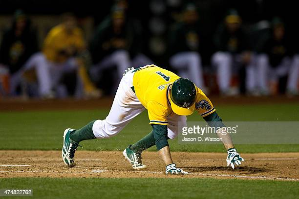 Billy Burns of the Oakland Athletics stumbles out of the batters box after bunting against the Detroit Tigers during the seventh inning at Oco...