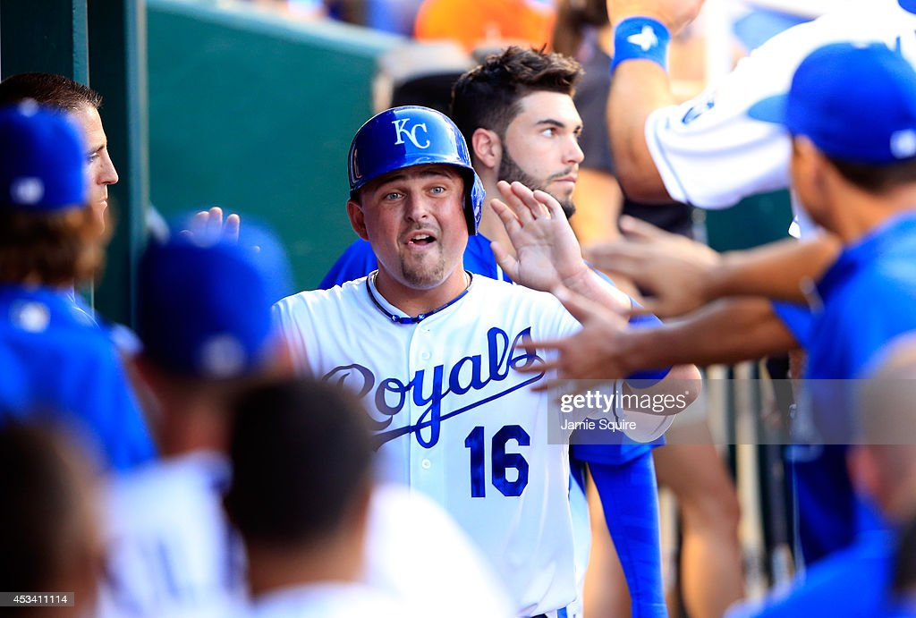 Billy Butler #16 of the Kansas City Royals is congratulated by teammates in the dugout after scoring during the 7th inning of the game against the San Francisco Giants at Kauffman Stadium on August 9, 2014 in Kansas City, Missouri.