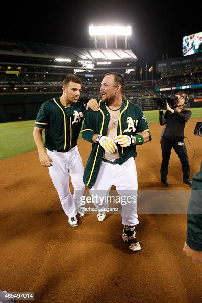 Billy Butler of the Oakland Athletics is congratulated by Danny Valencia after hitting a walkoff double following the game against the Los Angeles...