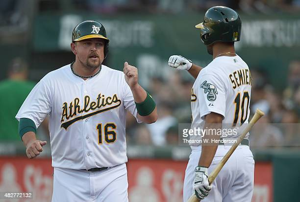 Billy Butler of the Oakland Athletics is congratulated by Marcus Semien after Butler scored against the Cleveland Indians in the bottom of the second...