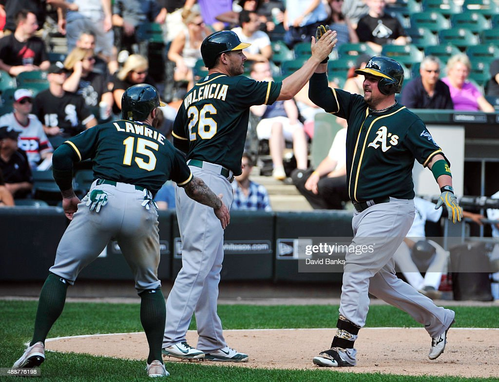 <a gi-track='captionPersonalityLinkClicked' href=/galleries/search?phrase=Billy+Butler&family=editorial&specificpeople=759092 ng-click='$event.stopPropagation()'>Billy Butler</a> #16 of the Oakland Athletics is greeted by <a gi-track='captionPersonalityLinkClicked' href=/galleries/search?phrase=Danny+Valencia&family=editorial&specificpeople=5443820 ng-click='$event.stopPropagation()'>Danny Valencia</a> #26 and <a gi-track='captionPersonalityLinkClicked' href=/galleries/search?phrase=Brett+Lawrie&family=editorial&specificpeople=5496694 ng-click='$event.stopPropagation()'>Brett Lawrie</a> #15 after hitting a three-run home run against the Chicago White Sox during the ninth inning on September 17, 2015 at U.S. Cellular Field in Chicago, Illinois. The A's won 4-2.