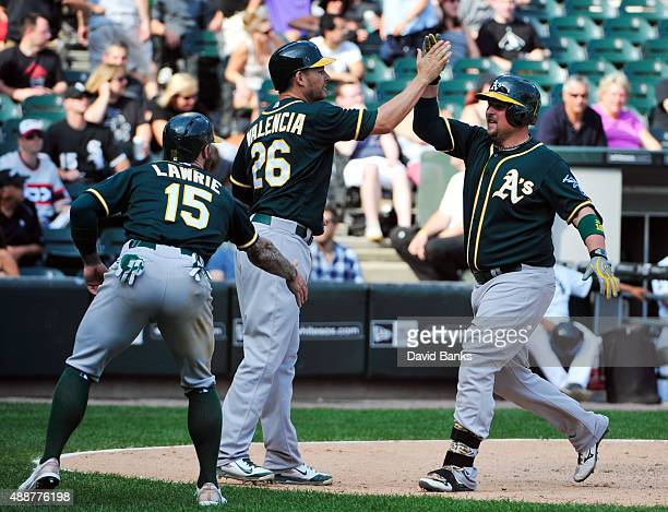 Billy Butler of the Oakland Athletics is greeted by Danny Valencia and Brett Lawrie after hitting a threerun home run against the Chicago White Sox...