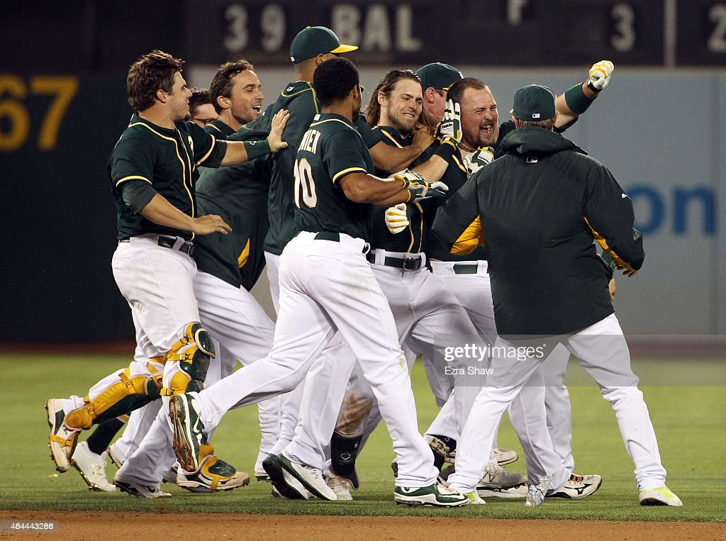 <a gi-track='captionPersonalityLinkClicked' href=/galleries/search?phrase=Billy+Butler&family=editorial&specificpeople=759092 ng-click='$event.stopPropagation()'>Billy Butler</a> #16 of the Oakland Athletics is surrounded by teammates after he hit in the winning run against the Los Angeles Dodgers in the tenth inning at O.co Coliseum on August 18, 2015 in Oakland, California.