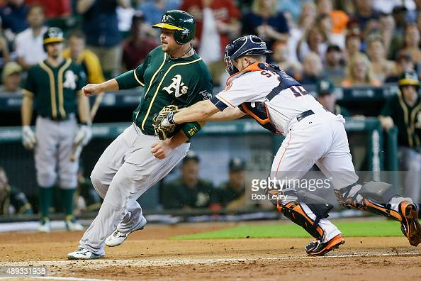 Billy Butler of the Oakland Athletics is tagged out by Max Stassi of the Houston Astros trying to score in the second inning at Minute Maid Park on...