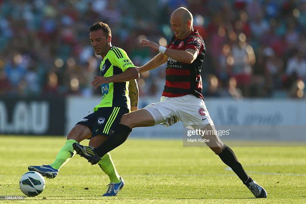 Billy Celeski of the Victory passes under pressure from Dino Kresinger of the Wanderers during the round 14 A-League match between the Western Sydney Wanderers and the Melbourne Victory at Parramatta Stadium on January 1, 2013 in Sydney, Australia.