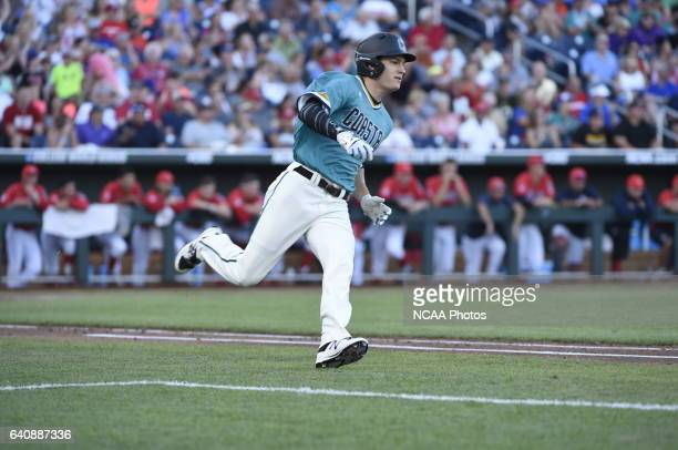Billy Cooke of Coastal Carolina University reaches safely with a hit against University of Arizona during the Division I Men's Baseball Championship...