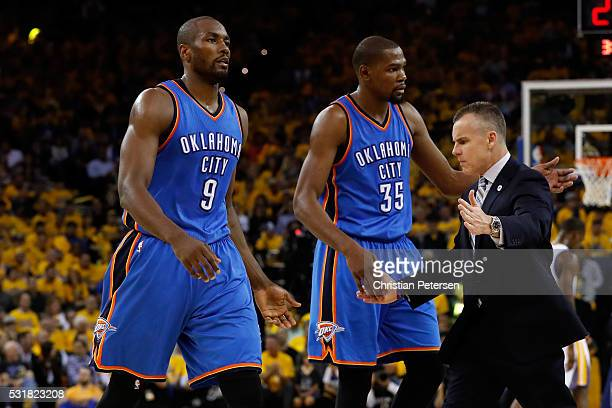 Billy Donovan of the Oklahoma City Thunder high fives Serge Ibaka and Kevin Durant during game one of the NBA Western Conference Finals against the...