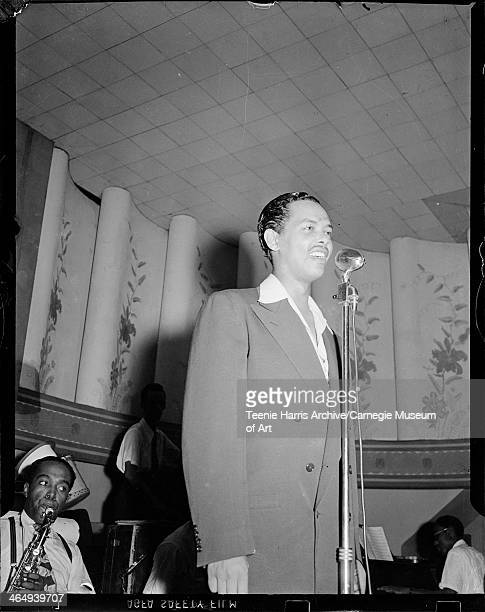 Billy Eckstine standing on stage beside microphone with his orchestra performing in background with saxophone player Charlie Parker in Aragon...
