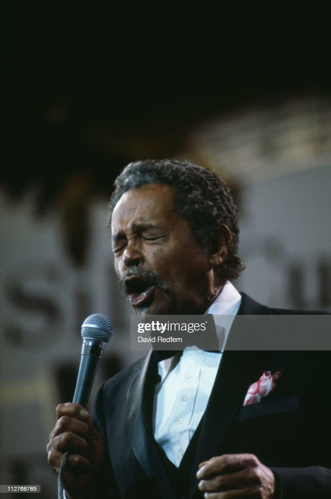 Billy Eckstine (1914-1993), U.S. jazz singer and band leader, singing into a microphone during a live concert performance, circa 1982.