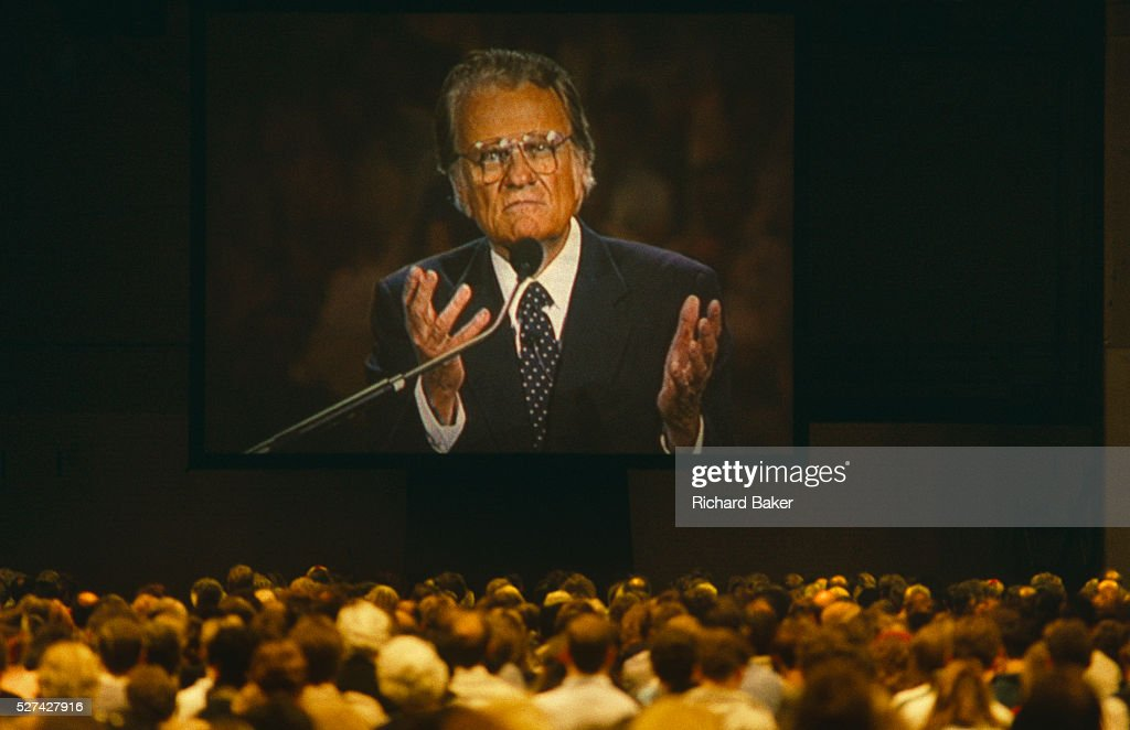 <a gi-track='captionPersonalityLinkClicked' href=/galleries/search?phrase=Billy+Graham+-+Evangelist&family=editorial&specificpeople=167098 ng-click='$event.stopPropagation()'>Billy Graham</a> preaches with sincere, confidently open hands to British Christians during Mission 89, a series of evangelical revival rallies in London, England. Graham is an Evangelical Christian who has been a spiritual adviser to several U.S. presidents including George W Bush with Time Magazine calling him '.. the nation's spiritual counselor.' He is number seven on Gallup's list of admired people for the 20th century and member of the Southern Baptist Convention. Here he is seen towering on a giant screen over the small heads of his UK congregation who are sitting passively listening to the message of this great man of God. The scale of his personality and presence above them makes this a powerful image of leadership and of followers.