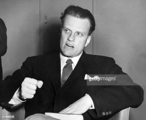 Billy Graham the American evangelist the Bible beneath his hand pounds his knee as he is interviewed aboard the liner 'United States' 26 February...