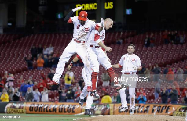Billy Hamilton and Joey Votto of the Cincinnati Reds celebrate after Hamilton hit a game winning double in the 10th inning against the Pittsburgh...