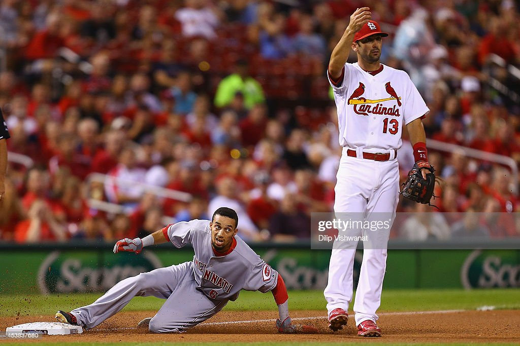 Billy Hamilton #6 of the Cincinnati Reds advances to third base after a failed pick off attempt at first base while Matt Carpenter #13 of the St. Louis Cardinals calls for the ball in the fourth inning at Busch Stadium on August 19, 2014 in St. Louis, Missouri.