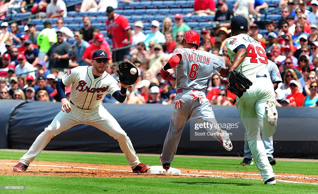 Billy Hamilton #6 of the Cincinnati Reds beats out an infield hit during the 3rd inning against <a gi-track='captionPersonalityLinkClicked' href=/galleries/search?phrase=Freddie+Freeman&family=editorial&specificpeople=5743987 ng-click='$event.stopPropagation()'>Freddie Freeman</a> #5 and <a gi-track='captionPersonalityLinkClicked' href=/galleries/search?phrase=Julio+Teheran&family=editorial&specificpeople=7091636 ng-click='$event.stopPropagation()'>Julio Teheran</a> #49 of the Atlanta Braves at Turner Field on April 27, 2014 in Atlanta, Georgia.