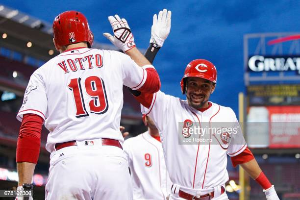 Billy Hamilton of the Cincinnati Reds celebrates with Joey Votto after hitting a threerun home run in the fourth inning of a game against the...