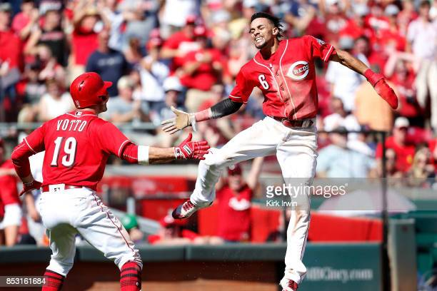 Billy Hamilton of the Cincinnati Reds is congratulated by Joey Votto of the Cincinnati Reds after scoring a run during the seventh inning of the game...