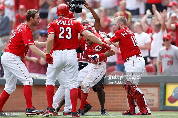 Billy Hamilton of the Cincinnati Reds is mobbed by teammates after scoring the winning run on a wild pitch in the ninth inning against the Milwaukee...