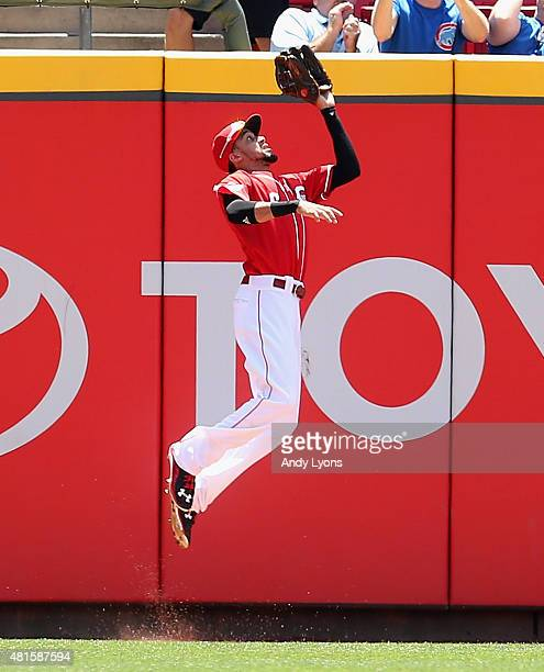 Billy Hamilton of the Cincinnati Reds jumps up to catch the ball hit by Kris Bryant of the Chicago Cubs in the second inning during the first game of...
