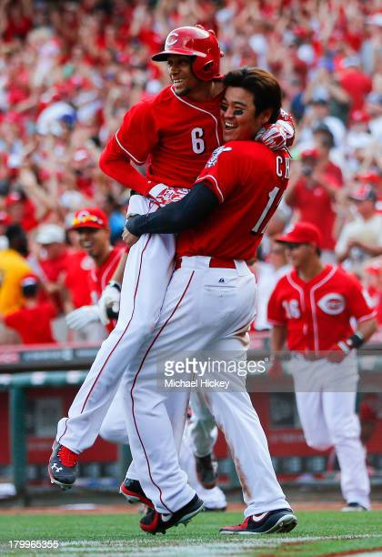 Billy Hamilton of the Cincinnati Reds leaps into the arms of ShinSoo Choo of the Cincinnati Reds after scoring the winning run in the tenth inning...