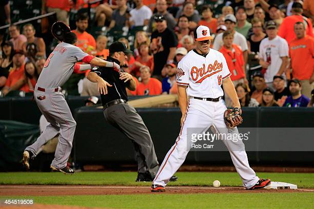 Billy Hamilton of the Cincinnati Reds runs into first base umpire Mike DiMuro after hitting an infield single as Chris Davis of the Baltimore Orioles...