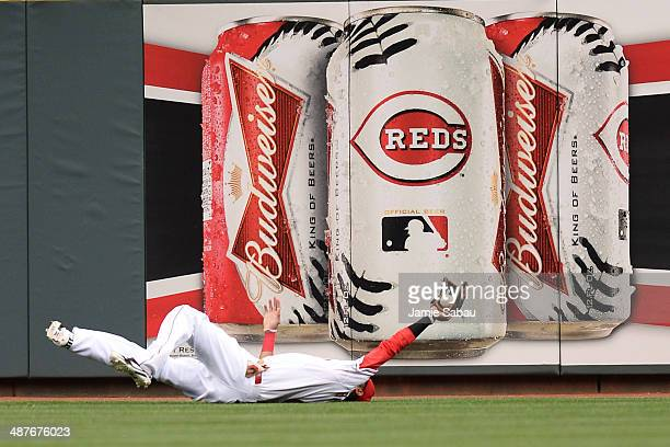 Billy Hamilton of the Cincinnati Reds shows umpires that he has made the diving catch off a line drive from Carlos Gomez of the Milwaukee Brewers in...