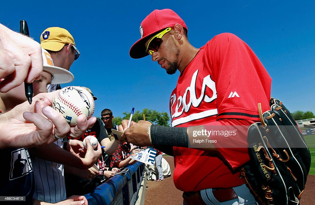 Billy Hamilton of the Cincinnati Reds signs autographs for fans before the start of a Cactus League spring training game against the Milwaukee...