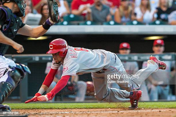 Billy Hamilton of the Cincinnati Reds slides in for a run ahead of a tag attempt by Nick Hundley of the Colorado Rockies in the fourth inning of game...