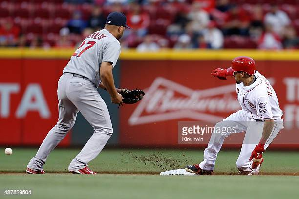 Billy Hamilton of the Cincinnati Reds slides into second base as the ball gets past Jhonny Peralta of the St Louis Cardinals during the first inning...