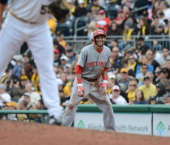 Billy Hamilton of the Cincinnati Reds smiles as he leads off first base as pitcher Brandon Cumpton of the Pittsburgh Pirates stands on the mound...