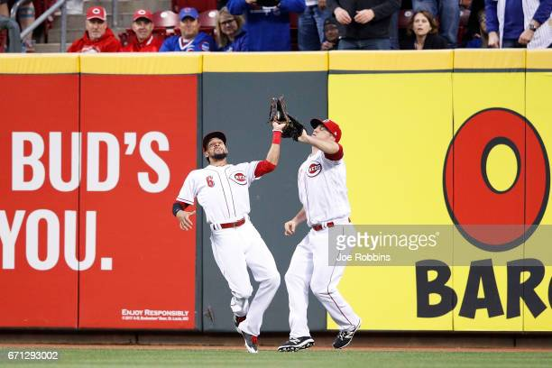 Billy Hamilton of the Cincinnati Reds steps in front of Scott Schebler to catch a fly ball near the right field wall in the third inning of a game...