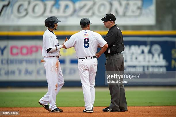 Billy Hamilton talks with the umpire and Jim Riggleman after being called out against the Montgomery Biscuits at Community Maritime Park Stadium on...
