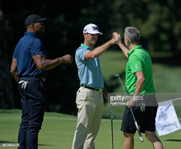 Billy Horschel and Michael Strahan fist bump Adam Rapport during a proam at THE NORTHERN TRUST at Glen Oaks Club on August 23 in Old Westbury New York