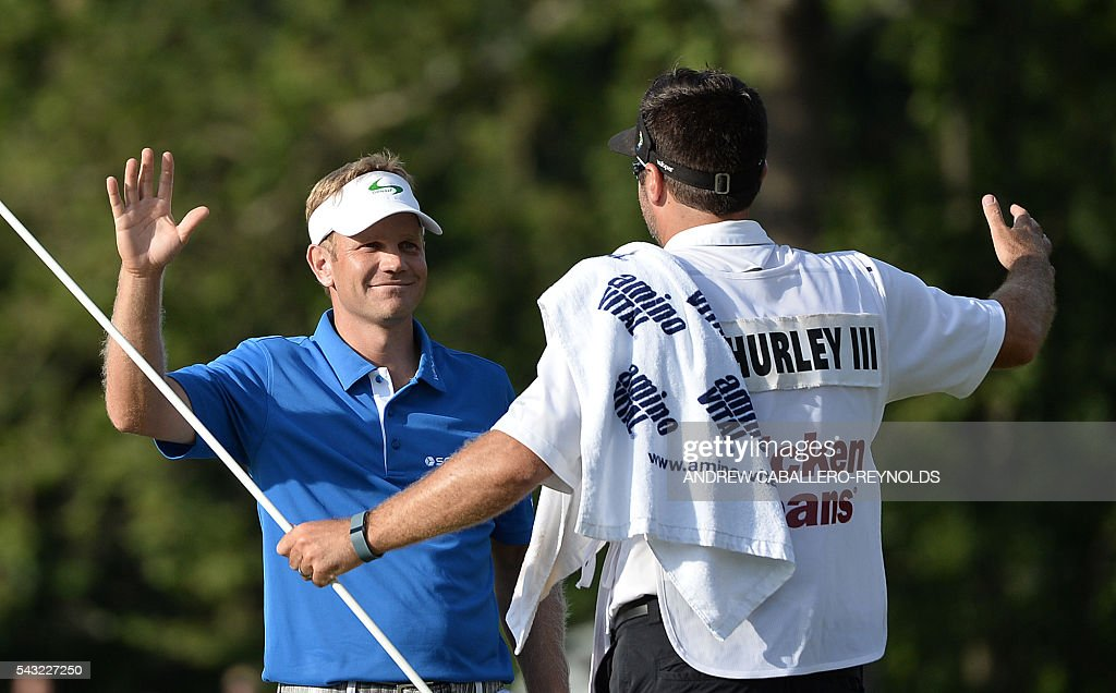 Billy Hurley III (L) greets his caddy after winning the Quicken Loans National at Congressional Country Club in Bethesda, Maryland on June 26, 2016.6. / AFP / ANDREW