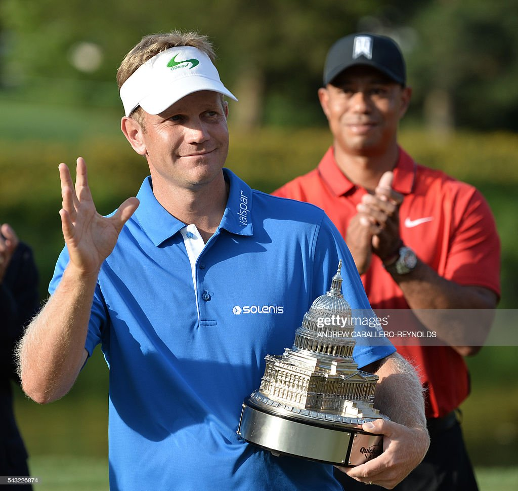 Billy Hurley III holds the trophy as Tiger Woods applauds after the final round of the Quicken Loans National at Congressional Country Club in Bethesda, Maryland on June 26, 2016. / AFP / ANDREW