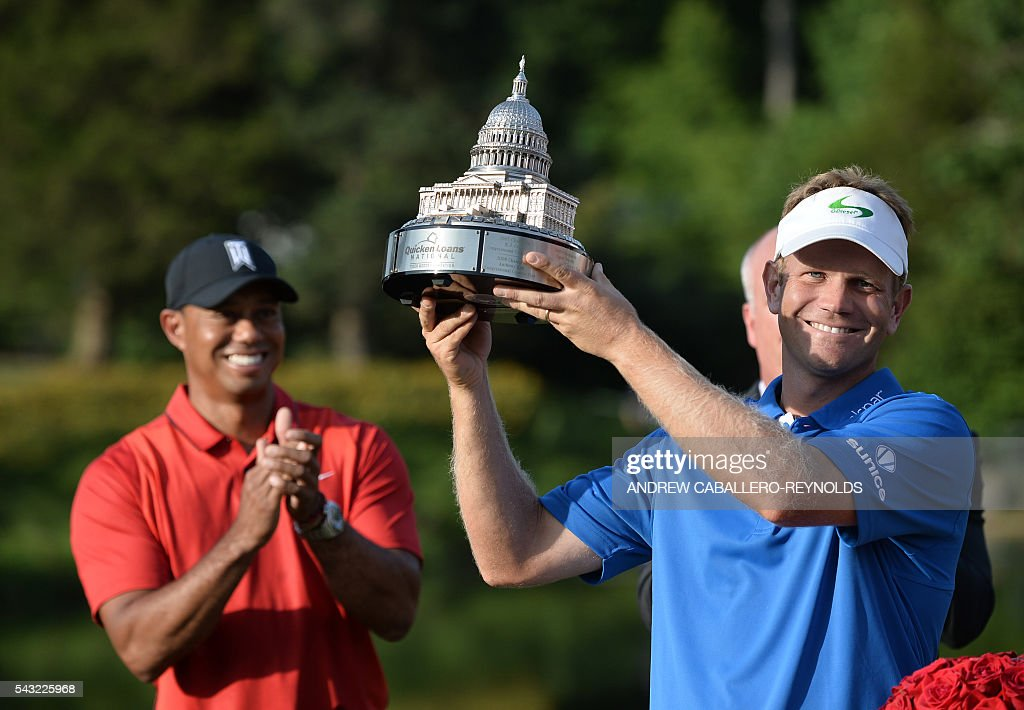 Billy Hurley III holds up the trophy as Tiger Woods looks on after the final round of the Quicken Loans National at Congressional Country Club in Bethesda, Maryland on June 25, 2016. / AFP / Andrew CABALLERO