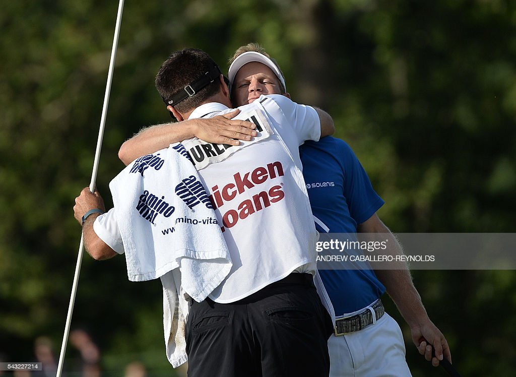 Billy Hurley III hugs his caddy after winning the Quicken Loans National at Congressional Country Club in Bethesda, Maryland on June 26, 2016. / AFP / ANDREW