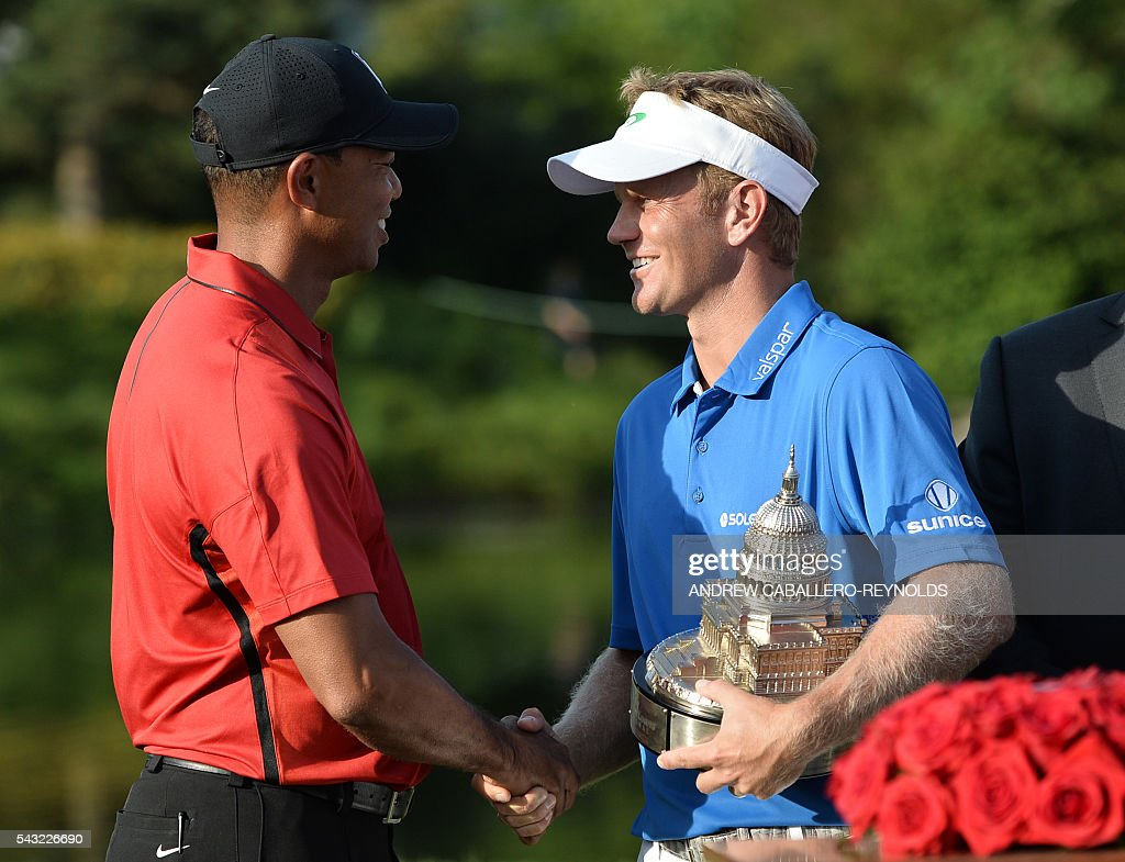 Billy Hurley III (R) shakes hands with Tiger Woods after the final round of the Quicken Loans National at Congressional Country Club in Bethesda, Maryland on on June 26, 2016. / AFP / ANDREW