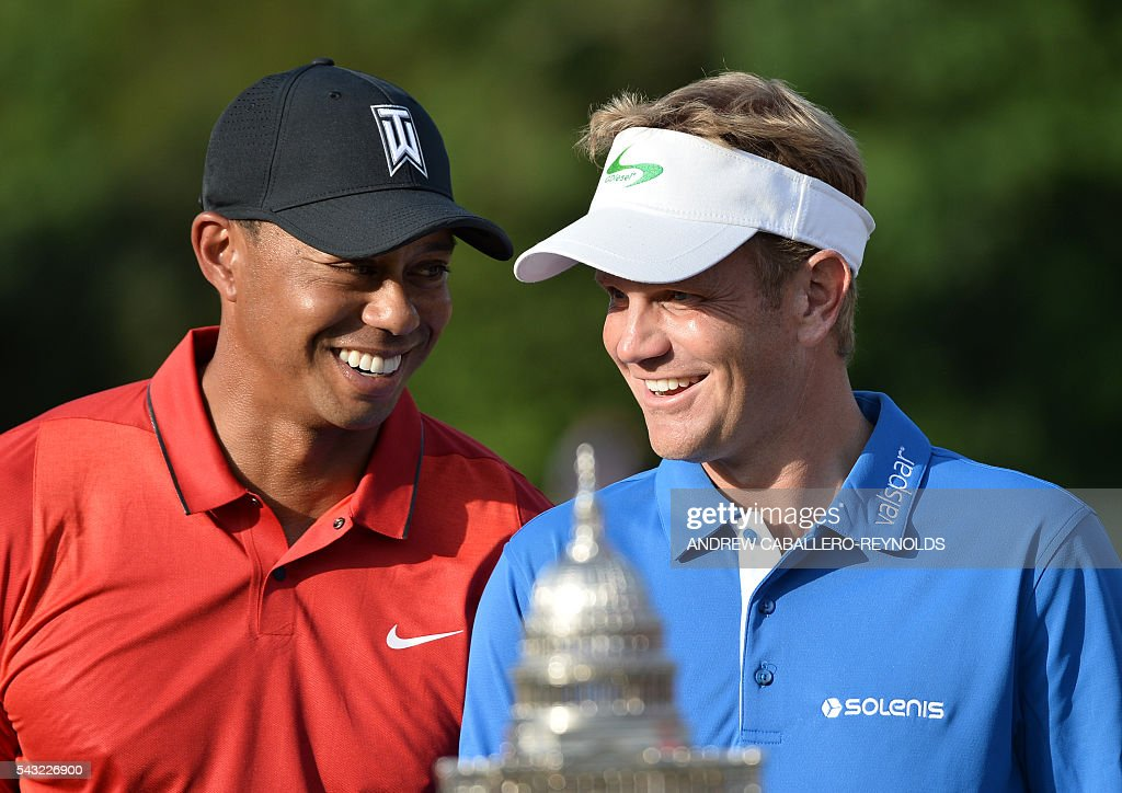Billy Hurley III (R) speaks with Tiger Woods after the final round of the Quicken Loans National at Congressional Country Club in Bethesda, Maryland on June 26, 2016. / AFP / ANDREW