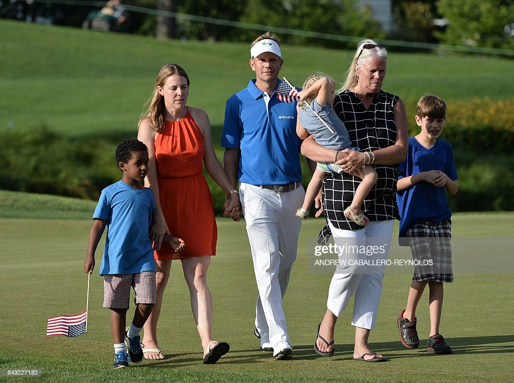 Billy Hurley III walks off the 18th green with his family after winning the Quicken Loans National at Congressional Country Club in Bethesda, Maryland on June 26, 2016. / AFP / ANDREW