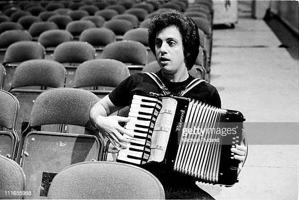 Billy Joel sits in the auditorium seating during a soundcheck playing accordion New York 7th December 1977