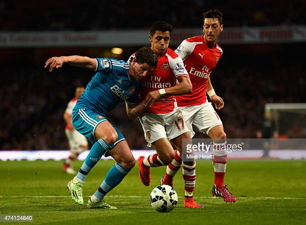 Billy Jones of Sunderland holds off Alexis Sanchez and Mesut Oezil of Arsenal during the Barclays Premier League match between Arsenal and Sunderland...