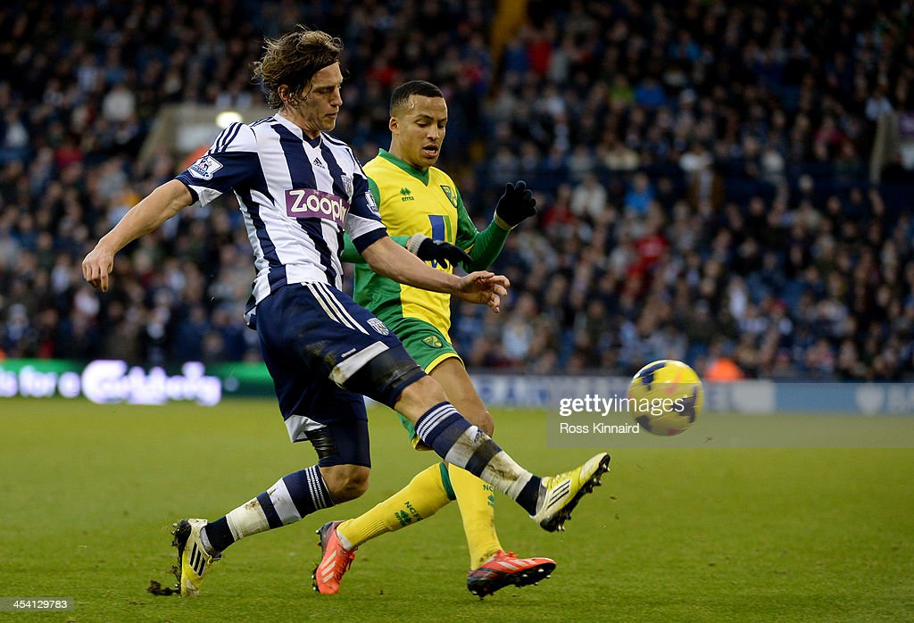Billy Jones of WBA is challenged Martin Olsson of Norwich during the Premier League match between West Bromwich Albion and Norwich City at The Hawthorns on December 7, 2013 in West Bromwich, England.